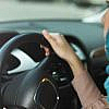 A woman holding the steering wheel of her car